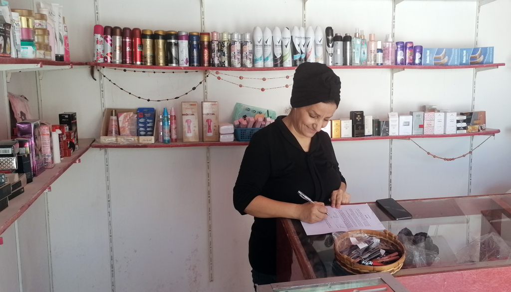Suhair fills out paperwork at her store, which she recently restocked through a loan from the NEF community revolving loan fund in Azraq, Jordan.