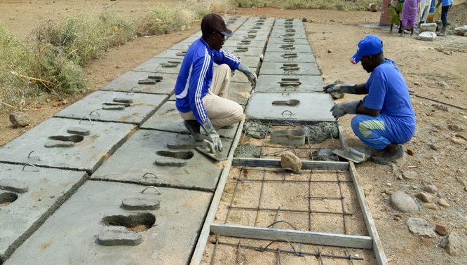 Local artisans at work fabricating latrine slabs