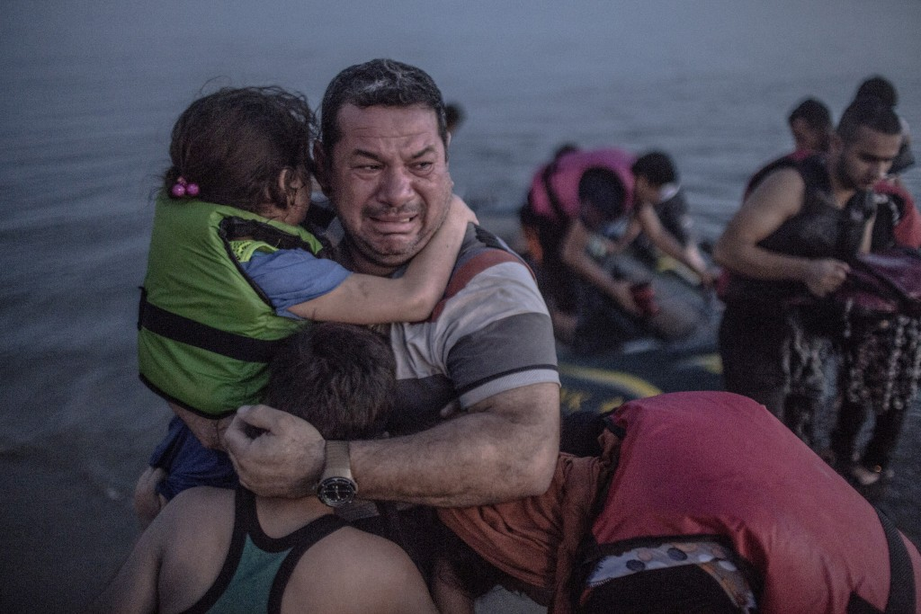 RETRANSMISSION TO CORRECT XNYT2 SENT AUG. 16, 2015, SLUGGED GREECE MIGRANTS 2, TO CHANGE COUNTRY OF ORIGIN OF FAMILY TO  IRAQ AND ADD NAME OF REFUGEE HOLDING CHILD TO LAITH MAJID.  CAPTION SHOULD READ AS FOLLOWS: Laith Majid, an Iraqi refugee breaks out in tears of joy, holding his son and daughter, after they  arrived safely in Kos, Greece on Aug. 15, 2015. The group crossed over from the Turkish resort town  of Bodrum and on the way their flimsy inflatable rubber boat, crammed with about 15 men, women  and children, lost  air.   (Daniel Etter/The New York Times)